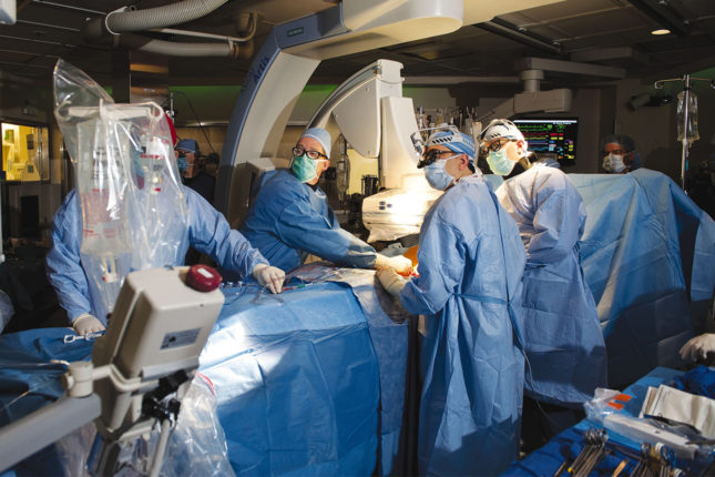 Left to right, cardiologist Alan Zajarias, MD, cardiac surgeon Hersh Maniar, MD, and fellow Brett Grizell, MD, perform a groundbreaking procedure that allows surgeons to implant new heart valves using catheters rather than open-heart surgery. Multidisciplinary collaboration is a key to the procedure's success.